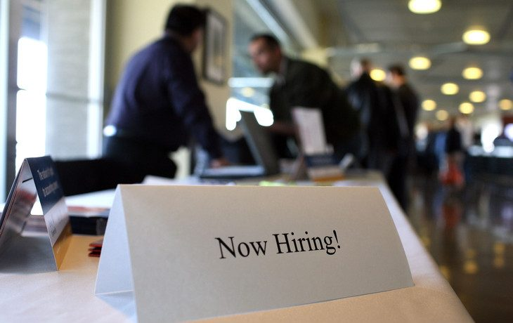 "A sign on top of a table, ""Now Hiring."""