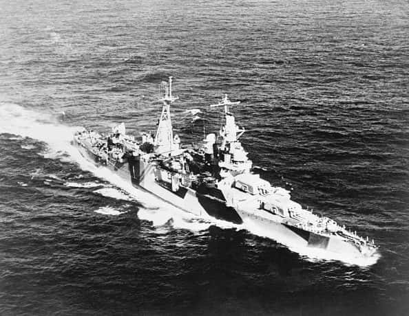 A black-and-white photo of the USS Indianapolis sailing across the Pacific Ocean