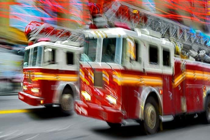 A photo of firetrucks driving to a fire