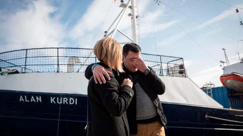 Abdullah Kurdi and his sister Tima embrace in front of a rescue ship named after his son