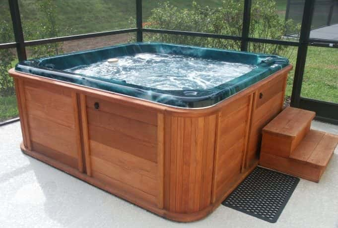 a wooden hot tub on a concrete deck, screen around