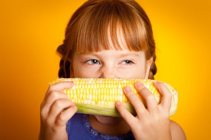 Color image of a little girl taking a bite of Corn on the cob, with orange background.