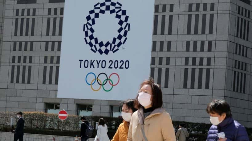 Olympic logo with people wearing masks