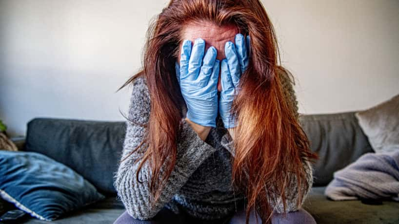 Woman with gloves covering her face