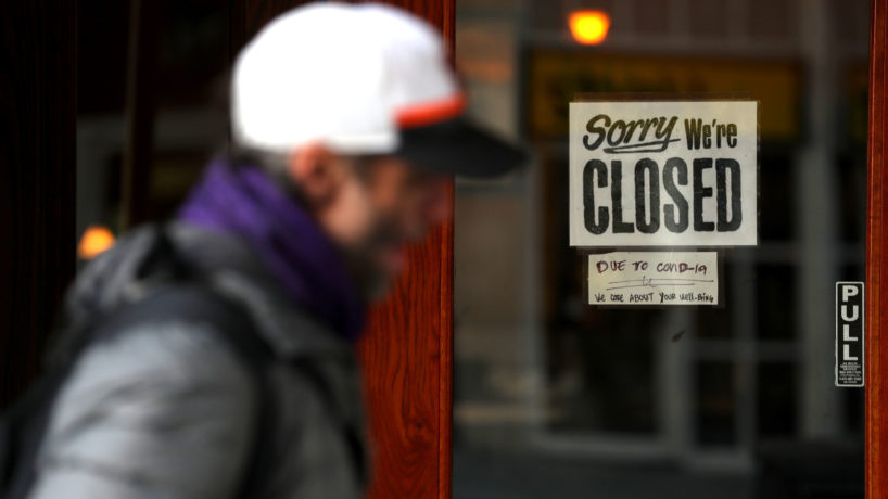 A pedestrian walks by a closed sign on the door of a restaurant on March 17, 2020 in San Francisco, California.