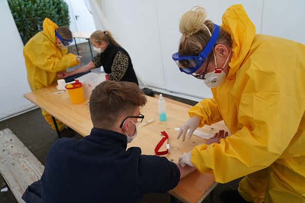 BERLIN, GERMANY - MARCH 27: Medical volunteers dressed in protective suits, masks, gloves and goggles take blood samples from visitors with symptoms to test them for Covid-19 infection in a tent set up next to a doctor's office on March 27, 2020 in Berlin, Germany. Doctor Ulrike Lipke said she set up the tent as a way to offer testing yet avoid possible coronavirus infection inside the premises of her practice. Germany is seeking to radically ramp up its coronavirus testing capacity to up to 200,000 tests per day by the end of April as a means to allow people to return to work and hence get the crisis-stricken German economy back into gear.