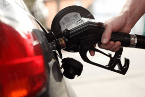 A photo of a man filling up his car with gas