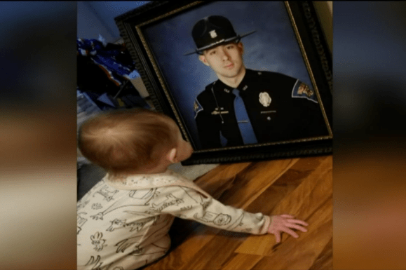 Young child staring at photograph of Indiana State Trooper.