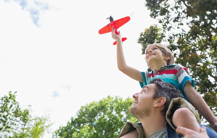 Boy with toy airplane sitting on father's shoulders