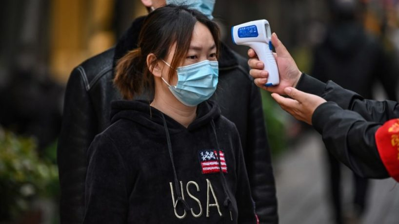 A woman wearing a face mask has her temperature checked by a volunteer at the entrance to a neighborhood in Wuhan, on April 2, 2020. - Wuhan, the central Chinese city where the coronavirus first emerged last year, partly reopened on March 28 after more than two months of near total isolation for its population of 11 million.