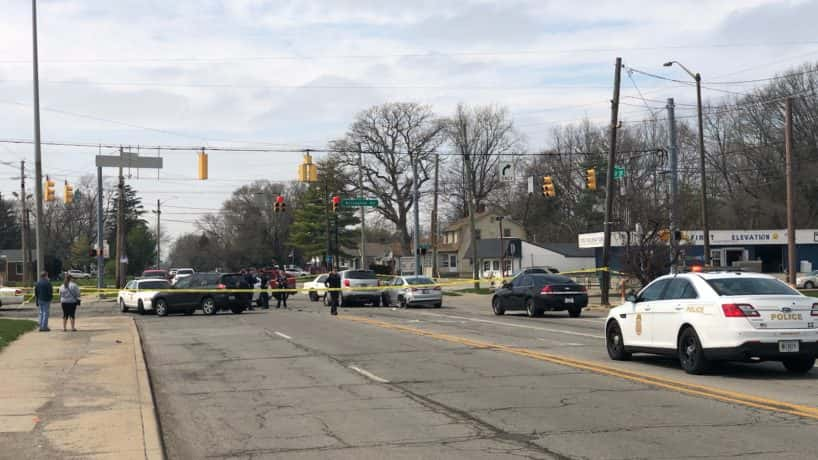 Crime tape and police cars at an intersection