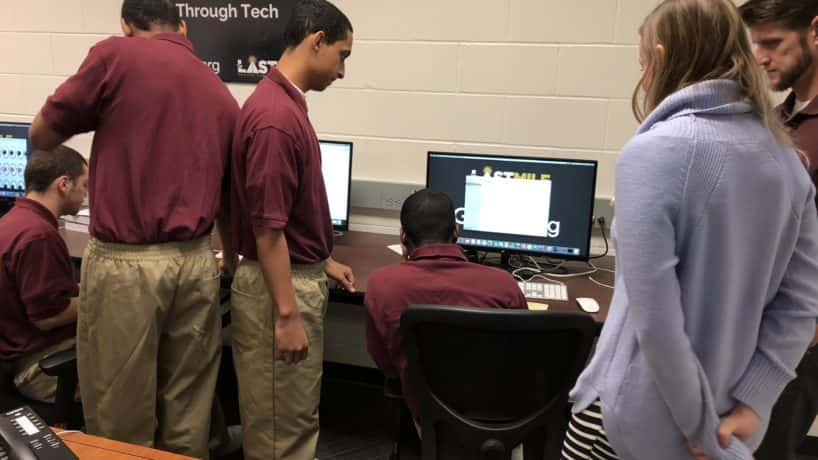 """Participants in Indiana's """"Last Mile"""" computer education program for prisoners gather around a computer monitor"""