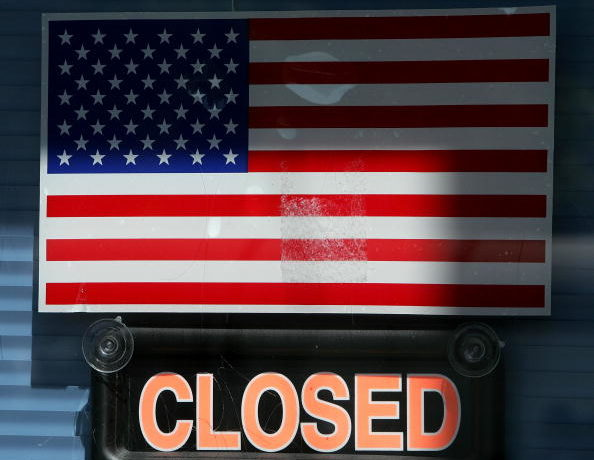 An American flag is seen next to a closed sign on a business .