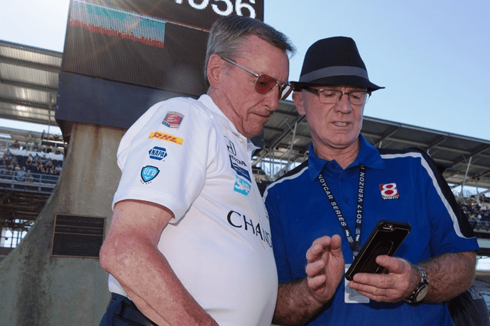 Derek Daly (R) with Johnny Rutherford (L) in front of the scoring pylon at Indianapolis Motor Speedway.
