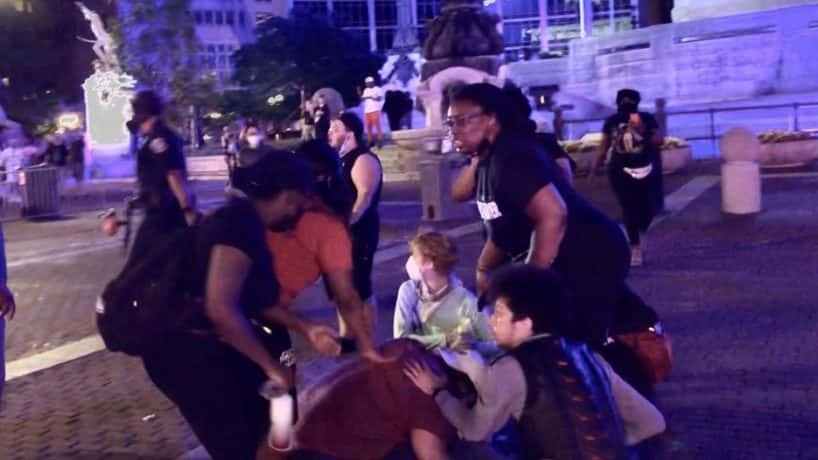 Protesters gather for an injured man