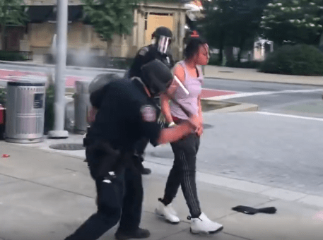A woman is whacked with a baton as she is arrested