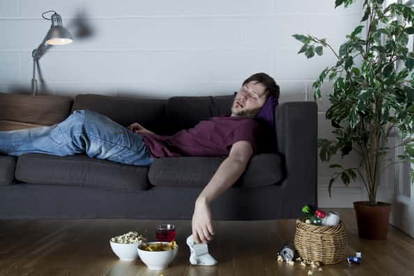 A photo of a man trying to sleep on the couch