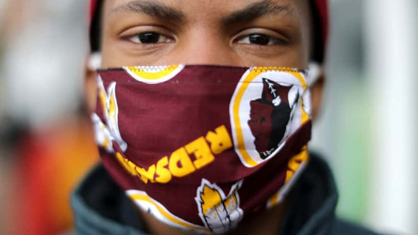 JoJo Houston wears a Washington Redskins face mask while helping Martha's Tabel distribute hundreds of free hot meals donated by the Clyde's Restaurant Group to people in need during the novel coronavirus pandemic, which has forced many people out of work and unable to reach healthy food, April 01, 2020 in Washington, DC. Martha's Table, a nonprofit organization that works to help underserved communities, is extending until April 24 its COVID-19 emergency response of financial and food support for people in need, including a weekly distribution of 6,570 bags of groceries at its public food sites in Southeast Washington, DC. (Photo by Chip Somodevilla/Getty Images)