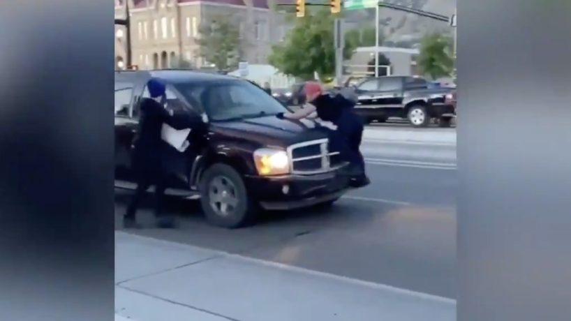 ANTIFA Protestor climbs on top of an SUV.