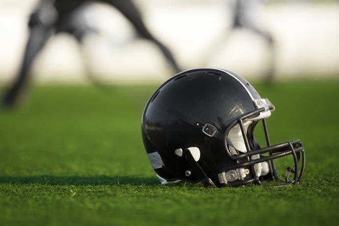 Black football helmet sitting on top of turf