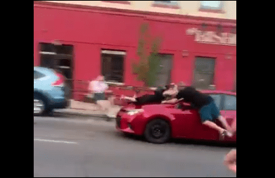 A photo of a red car hitting a protester taen and posted to Twitter.