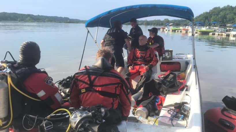 Search and rescue team members and firefighters in a boat on Eagle Creek Reservoir.