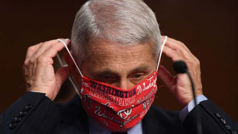 Dr. Anthony Fauci, director of the National Institute for Allergy and Infectious Diseases, lowers his face mask before testifying at a hearing of the Senate Health, Education, Labor and Pensions Committee on June 30, 2020 in Washington, DC. The committee is examining efforts to contain the Covid-19 pandemic while putting people back to work and kids back in school. (Photo by Kevin Dietsch-Pool/Getty Images)
