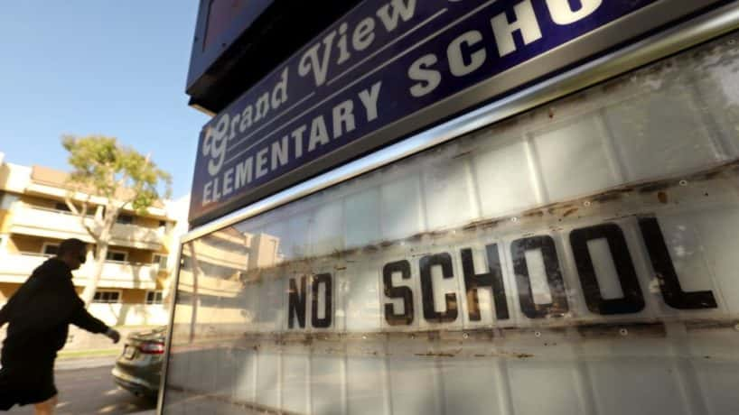 MAR VISTA, CA - JULY 13, 2020 - - A pedestrian walks past Grand View Boulevard Elementary School with a marquee that still reads, No School, in Mar Vista on July 13, 2020. Los Angeles campuses will not reopen for classes on Aug. 18, and the nations second-largest school system will continue with online learning until further notice, because of the worsening coronavirus surge, Supt. Austin Beutner announced Monday. Let me be crystal clear, Beutner said in an interview with The Times. We all know the best place for students to learn is in a school setting. But, he said, Were going in the wrong direction. And as much as we want to be back at schools and have students back at schools cant do it until its safe and appropriate.