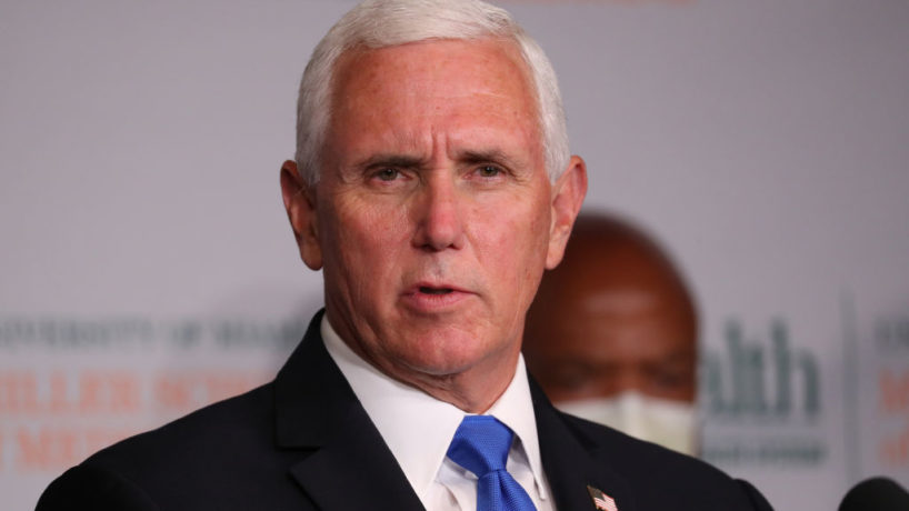 Mike Pence speaking at a press conference in a suit