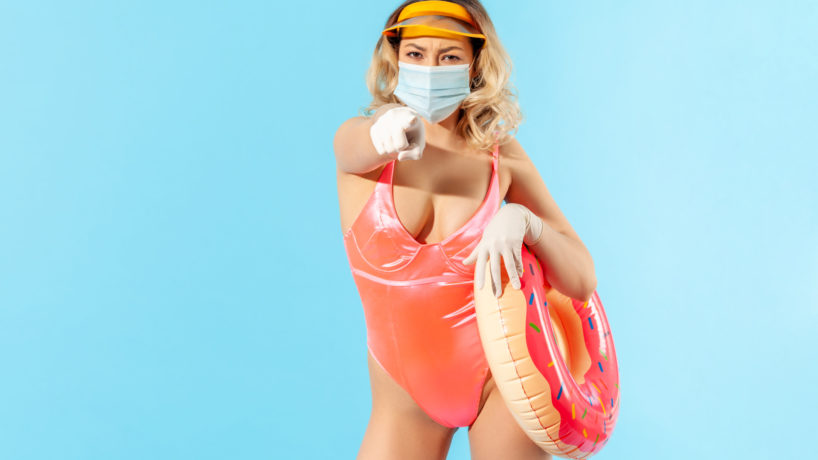 Bossy woman in swimsuit holding rubber ring, wearing hygienic face mask and gloves to prevent contagious coronavirus on resort beach, pointing finger choosing you, summer with covid-19. isolated
