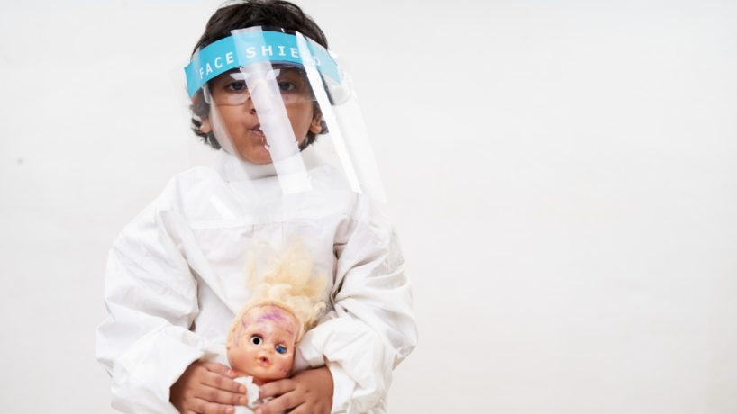 Little girls wearing face shield playing baby doll at hospital virus quarantine room
