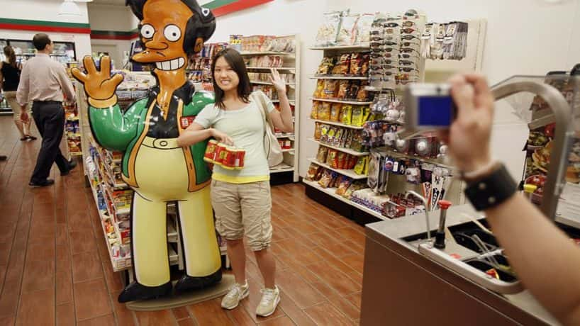 "Mandy Lui (C) of Toronto poses with larger than life ""Apu"" from the television cartoon show ""The Simpsons"" at a 7-11 store on 345 W. 42nd Street, converted into a Kwik-E-Mart to promote ""The Simpsons Movie"" opening next month, July 2, 2007 in New York City. The fictional Kwik-E-Mart is selling products from the cartoon -- like, KrustyO's cereal, Buzz Cola, and Squishees. (Photo by Michael Nagle/Getty Images)"
