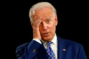 Joe Biden grabs his head, wandering off from his handlers.