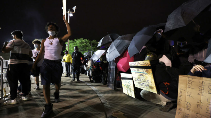 Demonstrators shield themselves during a standoff with police officers in front of the Public Safety Building after a peaceful march for Daniel Prude on September 07, 2020 in Rochester, New York. This is the sixth consecutive night of protesting since the family released bodycam footage of Daniel Prude's arrest that led to his subsequent death. Since protesting began, Rochester Mayor Lovely Warren announced the suspension of seven officers involved in the arrest and promises reforms to the city's police department. (Photo by Michael M. Santiago/Getty Images)