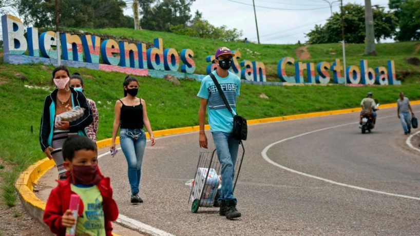 People wearing face masks walk along a street with a sign reading Welcome to San Cristobal in the background, in downtown San Cristobal, Venezuela, on September 1, 2020, amid the new coronavirus pandemic. - According to official figures, 100,000 Venezuelans who fled to Colombia due to the crisis in their country, are now returning after losing their jobs there amid the economic impacts of new coronavirus pandemic. Upon their arrival, they need to spend a quarantine at Points of Social and Integral Assistance (PASI), where they denounce having allegedly starved. (Photo by CARLOS EDUARDO RAMIREZ / AFP) (Photo by CARLOS EDUARDO RAMIREZ/AFP via Getty Images)