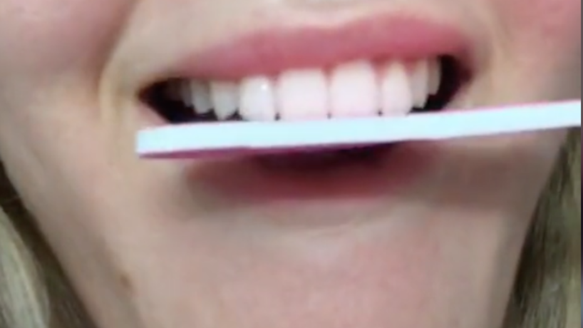 Young girl using nail file to file down teeth.