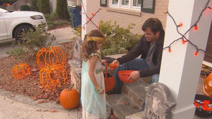 A man with a child painting pumpkins for Halloween in Greenfield