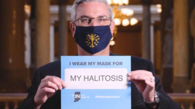 Indiana Governor Eric Holcomb holds a sign promoting wearing a mask in public.