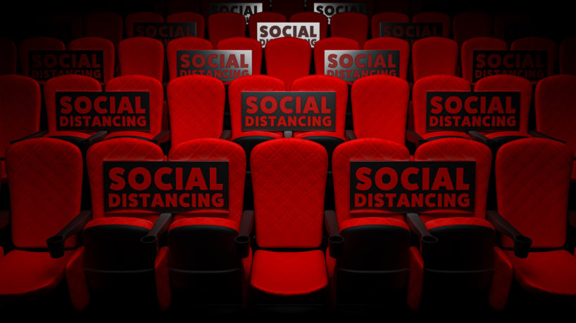 """A row of empty theater seats are marked with """"social distance"""" signs."""