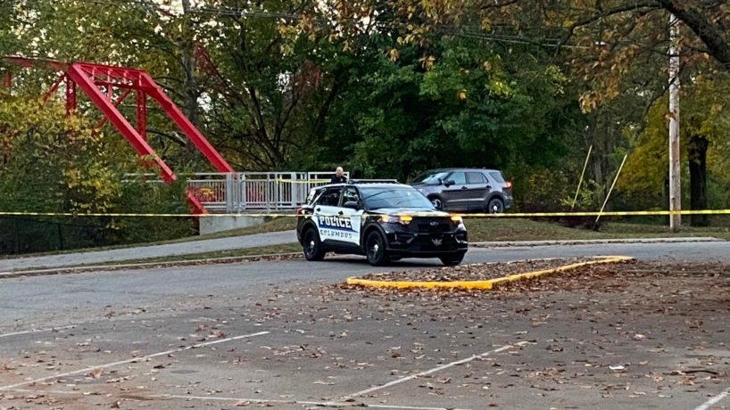 A Columbus, Ind. police vehicle in an empty parking lot surrounded by crime scene tape.