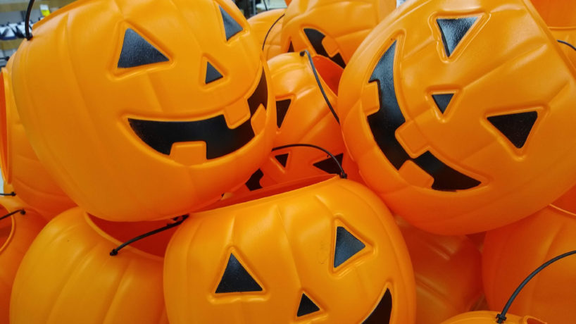 A stack of plastic, orange jack-o-lantern trick-or-treat baskets.