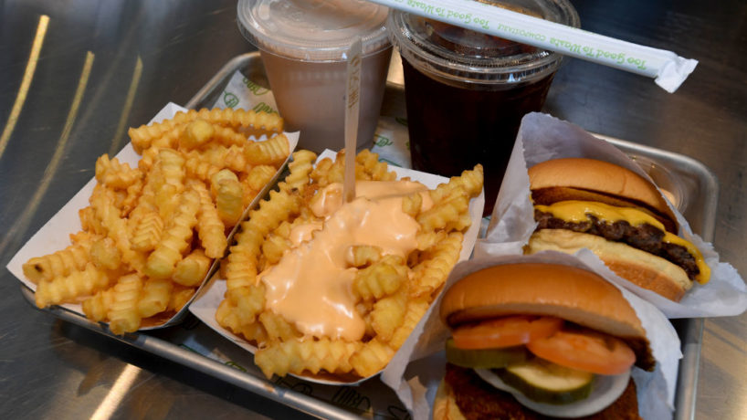 Fries, drinks, and burgers on a tray at a Shake Shack restaurant.
