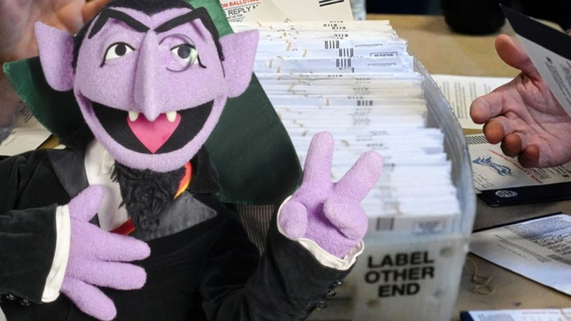 The Count from Sesame Street stands in front of a pile of election ballots.