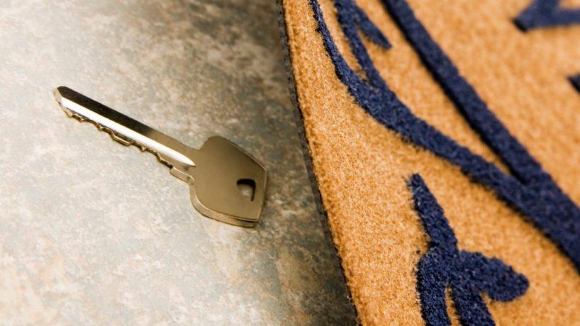 a house key lies under a welcome mat.