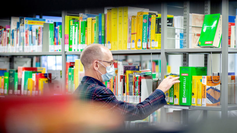 Michael Stünkel, head of the central municipal library, is standing at a shelf with dictionaries in various languages.