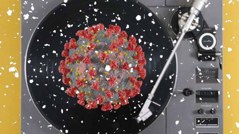 A turntable plays a record with a giant coronavirus sitting on top of it.