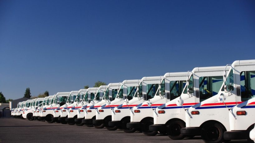 A fleet of U.S. postal trucks sits in a line outside of the USPS center.