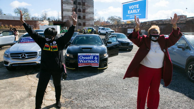 Gloria Tyson (L) and Gladys Ford (R) dance in front of their cars during a rally with Vice President-elect Kamala Harris and Georgia Democratic Senate candidates Rev. Raphael Warnock and Jon Ossoff at Bibb Mill Event Center on December 21, 2020 in Columbus, Georgia. The visit by Vice President-elect Harris comes ahead of a crucial runoff election for Warnock and Ossoff on January 5th that will determine which party controls the United States Senate. (Photo by Jessica McGowan/Getty Images)