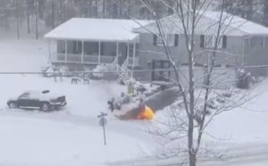 A man uses a flame thrower to clear the snow from his driveway.