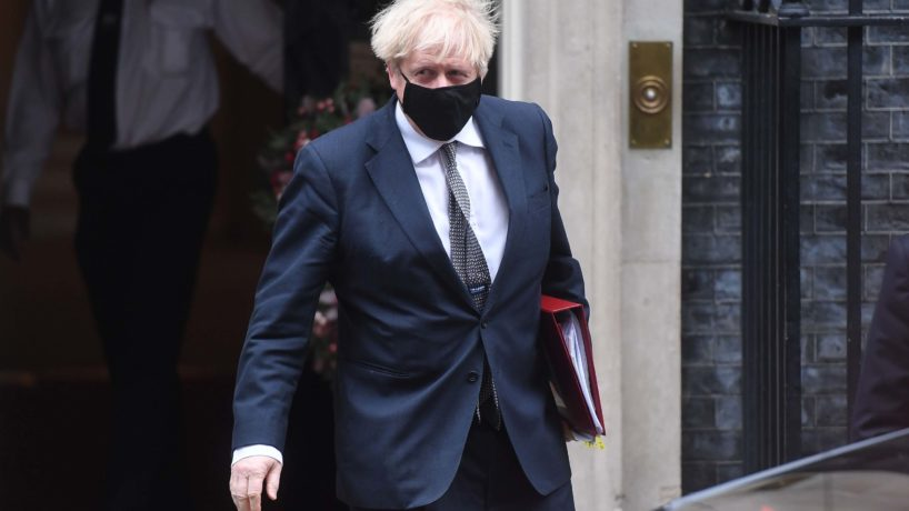 Picture of United Kingdom Prime Minister Boris Johnson walking while wearing a face mask.